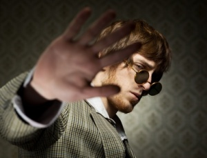 1960s style guy posing with circular glasses on vintage wallpaper background.